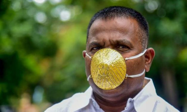 Un Indien porte un masque en or pour se protéger du coronavirus
